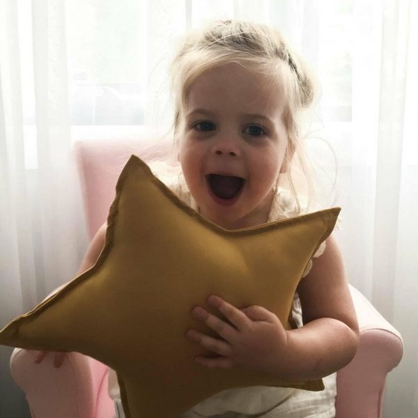 Girls Joy - Girl holding Medium Mustard Star Cushion