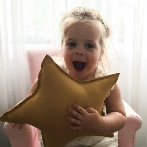 Girls Joy - Girl holding Medium Mustard Star Cushion