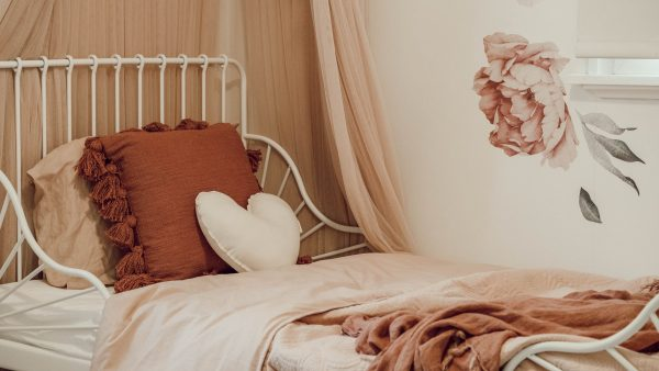 Girls Bedroom vintage boho theme - floral decals, rust coloured bedding, canopy and medium natural heart cushion