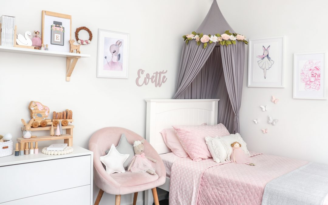 Designing a Room for Your Child - Girls Bedroom in pinks, white and grey. Grey canopy over bed with pink bedding, pink bedside chair, name plaque, wooden decor items on shelf and a Medium Light Grey Star Cushion