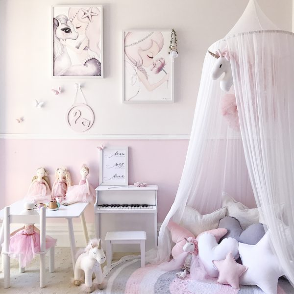 Girls Room in pink, white and grey including White Canopy, crochet rug, unicorn soft toys, kids piano, unicorn and mermaid artworks and Standard White Star Cushion, Medium White Heart Cushion, Small Baby Pink Star Cushion