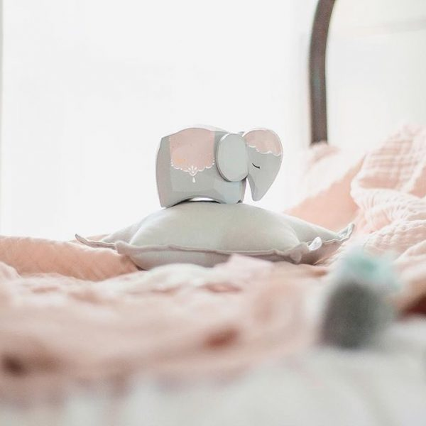 Closeup image featuring blush pink blanket, small wooden elephant and small light grey star cushion