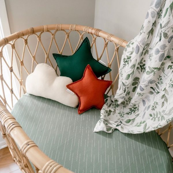 Rattan Bassinet with olive sheets, botanical leaf swaddle and Medium Forest Green Star Pillow, Small Rust Star Pillow and Small Natural Cloud Pillow