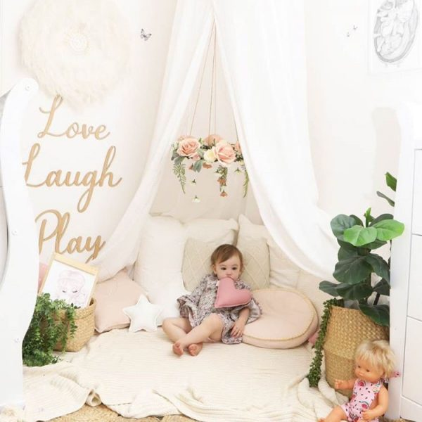 Cushion Corner with White Canopy, Floral Mobile, Rattan Baskets with plants in them, jute rug on floor and toddler laying amongst the cushions under the canopy including a dusty pink dolls heart cushion and white dolls star cushion