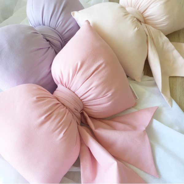 Closeup image featuring rose pink, lilac and baby pink bow cushions